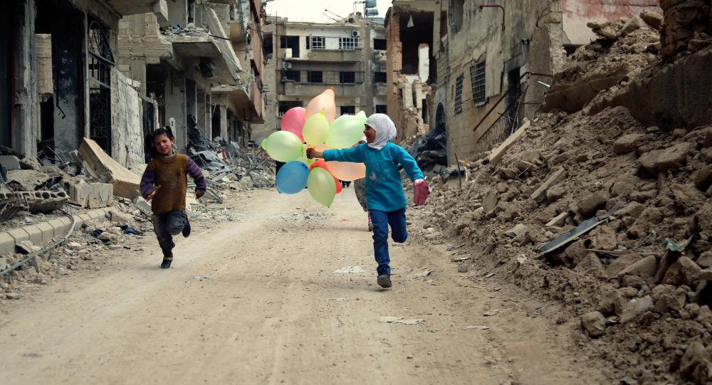 فتاتان تلهوان في شارع دمرته الحرب